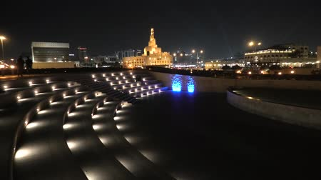 mosque doha : Stairs of small amphitheater at Souq Waqif Garden near Doha Corniche with Doha mosque at night. Doha city center in Qatar, Middle East, Arabian Peninsula in Persian Gulf. Stock Footage