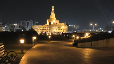 lugar famoso : Bench and walkway in Souq Waqif Garden near Doha Corniche with Doha mosque on background. Doha center in Qatar, Middle East, Arabian Peninsula in Persian Gulf at night.