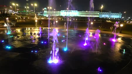 mosque doha : TIME LAPSE: Colored water fountain at Souq Waqif Park at Doha Corniche with Al shaykh Mosque illuminated at night on background. Doha city of Qatar, Middle East, Arabian Peninsula in Persian Gulf.