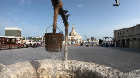 persiano : Doha, Qatar - February 20, 2019: pigeons at old well fountain, famous landmark at Souq Waqif. Middle East, Arabian Peninsula. Fanar Islamic Cultural Center with Spiral Mosque and Minaret on background