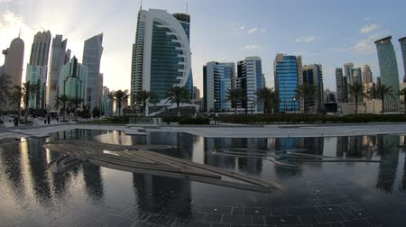 sheraton : Doha, Qatar - February 18,2019:Palm trees in West Bay park along corniche promenade with glassed high rises at sunset on background. Doha skyline, Qatar, Middle East, Arabian Peninsula in Persian Gulf