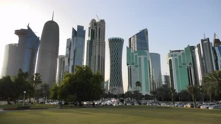 sheraton : Doha, Qatar - February 18, 2019:Doha West Bay high rises at sunset from green lawn along corchiche promenade. Modern skyscrapers of Doha skyline in Qatar,Middle East, Arabian Peninsula in Persian Gulf Stock Footage