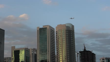 Doha, Qatar - February 18, 2019:Doha West Bay skyscrapers at twilight with plane flying on downtown. Glassed high rises of Doha skyline in Qatar, Middle East, Arabian Peninsula in Persian Gulf.
