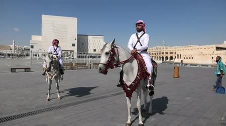 arabian horses : Doha, Qatar - February 20, 2019: two heritage Police Officers in traditional Qatari uniform riding white Arabian Horses at square of Souq Waqif. Popular tourist attraction in Doha city center. Stock Footage