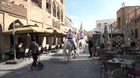 gigante : Doha, Qatar - February 20, 2019: two police officers riding white Arabian horses at Souq Waqif. Fanar Islamic Cultural Center with Spiral Mosque and golden giant thumb sculpture on background.