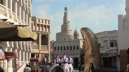 arabian horses : Doha, Qatar - February 20, 2019: police officers, famous attraction, riding white Arabian horses at Souq Waqif. Fanar Islamic Cultural Center with Mosque and golden giant thumb sculpture on background Stock Footage
