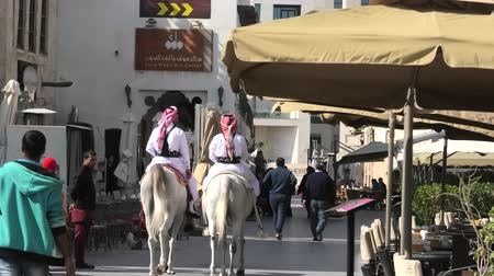 Doha, Qatar - February 20, 2019: Police on horse at Souq Waqif riding white Arabian Horses. Popular tourist attraction in Middle East, Arabian Peninsula. Стоковые видеозаписи