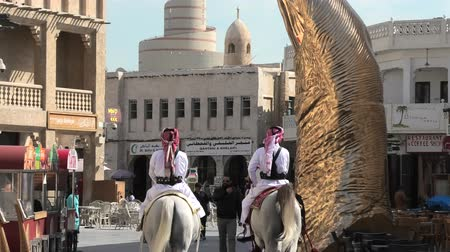Doha, Qatar - February 20, 2019: two police officers riding white Arabian horses at Souq Waqif market. Fanar Islamic Cultural Center with Spiral Mosque and golden giant thumb sculpture on background.