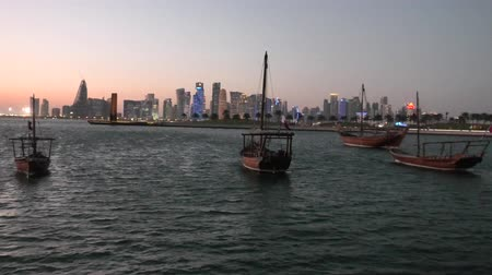 mia : Scenary seafront landscape of Doha Bay at sunset. Traditional dhows and West bay skyline at evening. Urban cityscape of Doha, Qatari capital. Middle East, Arabian Peninsula in Persian Gulf.