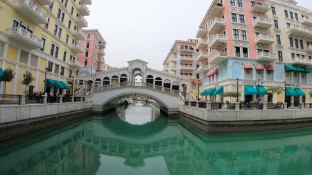 Doha, Qatar - February 20, 2019:Venetian Rialto bridge replica of picturesque district of Doha, Qatar. Venice at Qanat Quartier in the Pearl-Qatar. Famous tourist attraction at sunlight. Стоковые видеозаписи