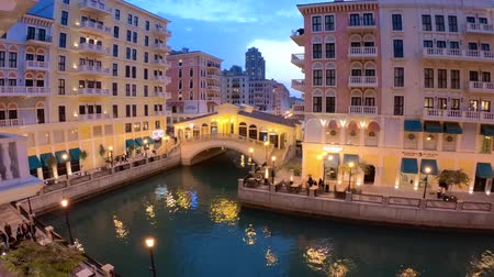 Doha, Qatar - February 20, 2019:Aerial view of Venetian Rialto bridge on canals of picturesque and luxurious district of Doha at twilight. Scenary of Venice at Qanat Quartier in the Pearl-Qatar. Стоковые видеозаписи