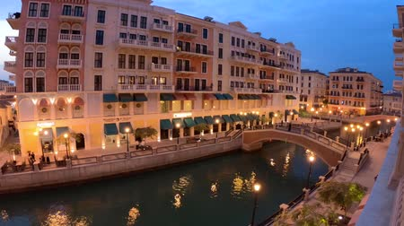 Doha, Qatar - February 20, 2019:two Venetian bridges on canals of picturesque district icon of Doha illuminated at night. Panorama of Venice at Qanat Quartier, the Pearl-Qatar, Middle East at twilight