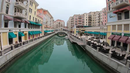 Doha, Qatar - February 20, 2019:Venice at Qanat Quartier in the Pearl, Persian Gulf, Middle East. Panoramic view of Venetian Rialto bridge replica on canals of picturesque district of Doha city.