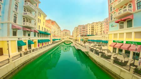 Doha, Qatar - February 20, 2019: TIME LAPSE of Venice at Qanat Quartier in the Pearl-Qatar. Aerial view of Venetian Rialto bridge replica reflecting on canals of picturesque district icon of Doha.