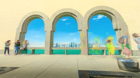 Doha, Qatar - February 20, 2019:Courtyard of Museum of Islamic Art with arched windows opening view on Doha West Bay skyline and Persian Gulf. Arabs and tourists visit the popular museum. TIME LAPSE