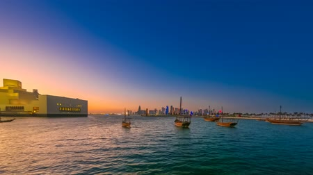 mia : TIME LAPSE: seafront landscape of Doha Bay after sunset. Traditional dhows and West bay skyline at evening. Urban cityscape of Doha, Qatari capital. Middle East, Arabian Peninsula in Persian Gulf. Stock Footage