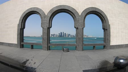 mia : Panorama of Doha West Bay skyline through arched windows opening view on Doha Bay. Dohas waterfront near Corniche. Doha in Qatar seafront. Middle East, Arabian Peninsula, Persian Gulf.