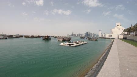 mia : Doha seafront with palm trees and West Bay skyline along Corniche in Qatari capital with Dhow Harbour in a sunny day. Doha in Qatar. Middle East, Arabian Peninsula, Persian Gulf.