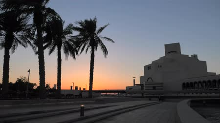mia : Scenic seafront landscape of Doha Bay Park with palm trees and dhow at sunset sky. Urban cityscape of Doha, Qatari capital. Middle East, Arabian Peninsula in Persian Gulf.