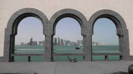 mia : Modern skyscrapers of Doha West Bay skyline at sunset light through arches of museum located along Corniche in Qatari capital. Doha in Qatar. Middle East, Arabian Peninsula in Persian Gulf.