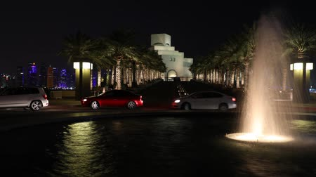 Doha, Qatar - February 20, 2019: TIME LAPSE of fountain reflecting at Corniche with skyscrapers of West Bay skyline on background. Museum of Islamic Art at night.