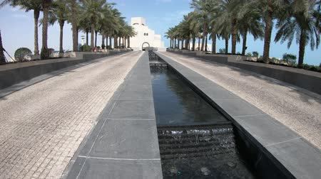 Doha, Qatar - February 16, 2019: MIA park with palm trees and water feature of Museum of Islamic Art in Doha city near Corniche and Dohas Waterfront. Middle East, Persian Gulf. Sunny blue sky. Стоковые видеозаписи