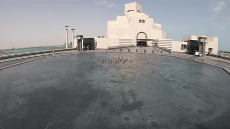 Doha, Qatar - February 16, 2019:Fountain water reflecting Museum of Islamic Art, near Corniche with skyscrapers of West Bay skyline on background. Doha, Qatari capital, in Middle East.