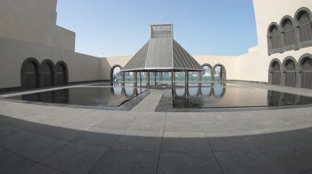 mia : Doha, Qatar - February 16, 2019: Courtyard of Museum of Islamic Art with fountains and arched windows opening view on Doha West Bay and Persian Gulf reflecting in a pool. Stock Footage