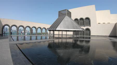 mia : Doha, Qatar - February 16, 2019: courtyard of Museum of Islamic Art with fountains and arched windows opening view on Doha West Bay and Persian Gulf reflecting in a pool. Wide angle view.