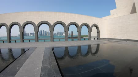mia : Doha, Qatar - February 16, 2019: series of arches reflections in a pool fountain inside Museum of Islamic Art. Popular tourist seafront. Middle East, Persian Gulf. Doha West Bay skyline on background. Stock Footage