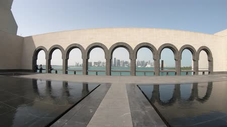 mia : Doha, Qatar - February 16, 2019: view of arched walkway and reflecting pools at Museum of Islamic Art or MIA. Doha West Bay and Persian Gulf on background. Seafront of Doha Bay. Sunny day.