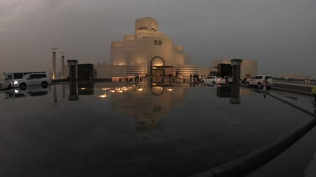 mia : Doha, Qatar - February 20, 2019:Fountain water reflecting Museum of Islamic Art at night, near Corniche with skyscrapers of West Bay skyline on background. Doha, Qatari capital, in Middle East.