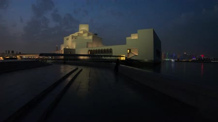 mia : Doha, Qatar - February 20, 2019:Doha seafront and West Bay skyline reflecting in Doha Bay at Museum of Islamic Art. Corniche in Qatari capital. Scenic night sky. Qatar in Middle East, Persian Gulf.