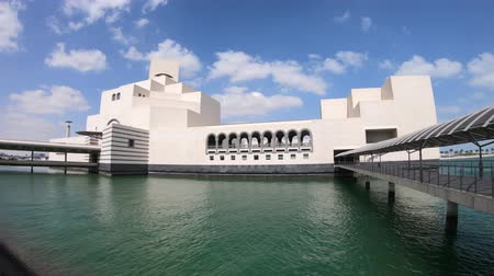 mia : Doha, Qatar - February 20, 2019: Museum of Islamic Art in Doha Bay, icon of urban cityscape. Qatari capital in Middle East, Arabian Peninsula, Persian Gulf. View from Mia Park with cloudy sky. Stock Footage