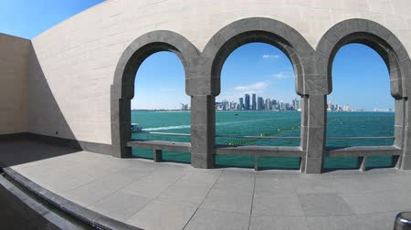 mia : Doha, Qatar - February 20, 2019:Wide angle view of arches of Museum of Islamic Art and Doha West Bay skyline in a sunny day. Dohas waterfront near Corniche. Middle East in Persian Gulf.