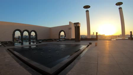 mia : Doha, Qatar - February 20, 2019: Courtyard of Museum of Islamic Art with fountains, benches and arched windows opening view on Doha city center and Persian Gulf. Scenic sunset light. Stock Footage