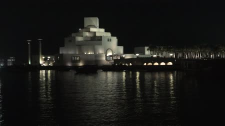 mia : Doha, Qatar - February 20, 2019:Doha Bay at twilight with Museum of Islamic Art. Traditional dhows and West bay skyline at blue hour. Urban cityscape of Doha, Qatari. Middle East, Arabian Peninsula. Stock Footage