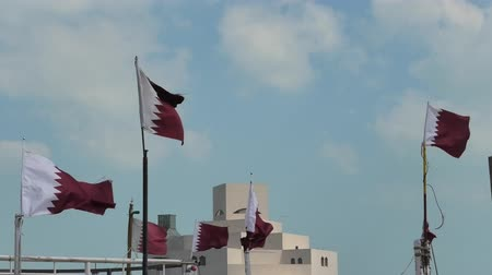 mia : Doha, Qatar - February 20, 2019: seafront landscape of Doha Bay. Museum of Islamic Art with Qatar flags of the traditional dhows boats in Doha city, the Qatari capital.
