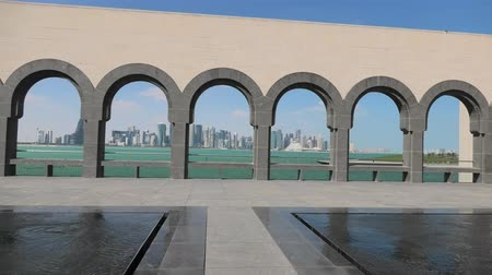 mia : Doha, Qatar - February 20, 2019: modern skyscrapers of Doha West Bay skyline through a series of arches in courtyard of Museum of Islamic Art. Popular tourist seafront. Middle East in Persian Gulf. Stock Footage