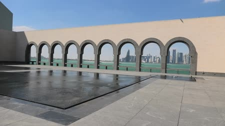 mia : Doha, Qatar - February 20, 2019: Doha West Bay skyline through arches in courtyard of Museum of Islamic Art along water features in a sunny day. Popular tourist seafront. Middle East in Persian Gulf. Stock Footage