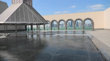 mia : Doha, Qatar - February 20, 2019: wide angle view of courtyard of Museum of Islamic Art with fountains and arched windows opening view on Doha West Bay and Persian Gulf reflecting in a pool. Stock Footage