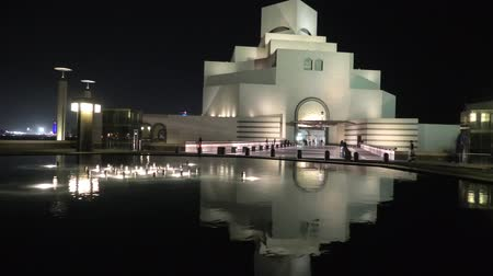mia : Doha, Qatar - February 16, 2019: Museum of Islamic Art, popular tourist attraction, along Corniche reflecting on fountain water in a night sky. Middle East, Arabian Peninsula, Persian Gulf. Stock Footage