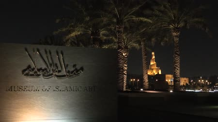mia : Doha, Qatar - February 20, 2019: Museum of Islamic Art sign and Fanar Islamic Cultural Center reflects in fountain water near Corniche promenade at night. Middle East, Arabian Peninsula, Persian Gulf.
