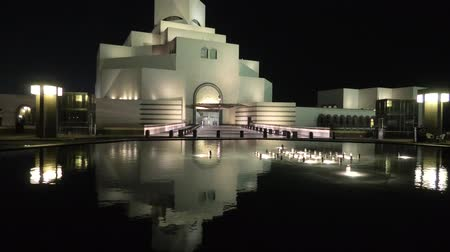 mia : Doha, Qatar - February 16, 2019: Museum of Islamic Art, along Corniche reflecting on fountain water in a night sky. Middle East, Arabian Peninsula, Persian Gulf.