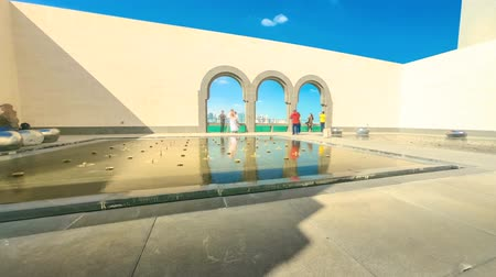 mia : Doha, Qatar - February 20, 2019:TIME LAPSE of courtyard of Museum of Islamic Art with arched windows opening view on Doha West Bay skyline and Persian Gulf. Tourists visit the popular museum.