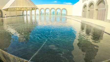 mia : Doha, Qatar - February 16, 2019: TIME LAPSE details of Museum of Islamic Art with fountains and arched windows opening view on Doha West Bay and Persian Gulf reflecting in a pool. Wide angle view.