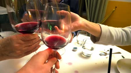 brazil : Close up of four hands with red wine glasses while doing cheers to celebrate in a restaurant, set table blurred on background.