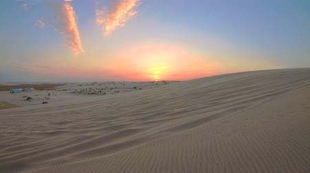vnitrozemí : TIME LAPSE at sunset in the desert sand dunes of Qatar and Saudi Arabia. Khor Al Udeid, Persian Gulf, Middle East. Discovery and adventure travel concept.