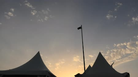 vnitrozemí : sunset in a desert camp with tents of Qatar, Khor Al Udeid, Persian Gulf, Middle East. Flag of Qatar waving high in the sunset sky with clouds.