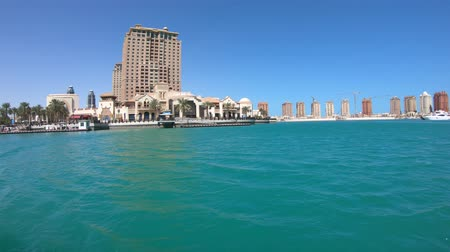 porto arabia : Sea view of Doha West Bay skyline with luxurious resort hotels with blue sky in Porto Arabia, The Pearl-Qatars main harbor in Doha city, Persian Gulf, Middle East.